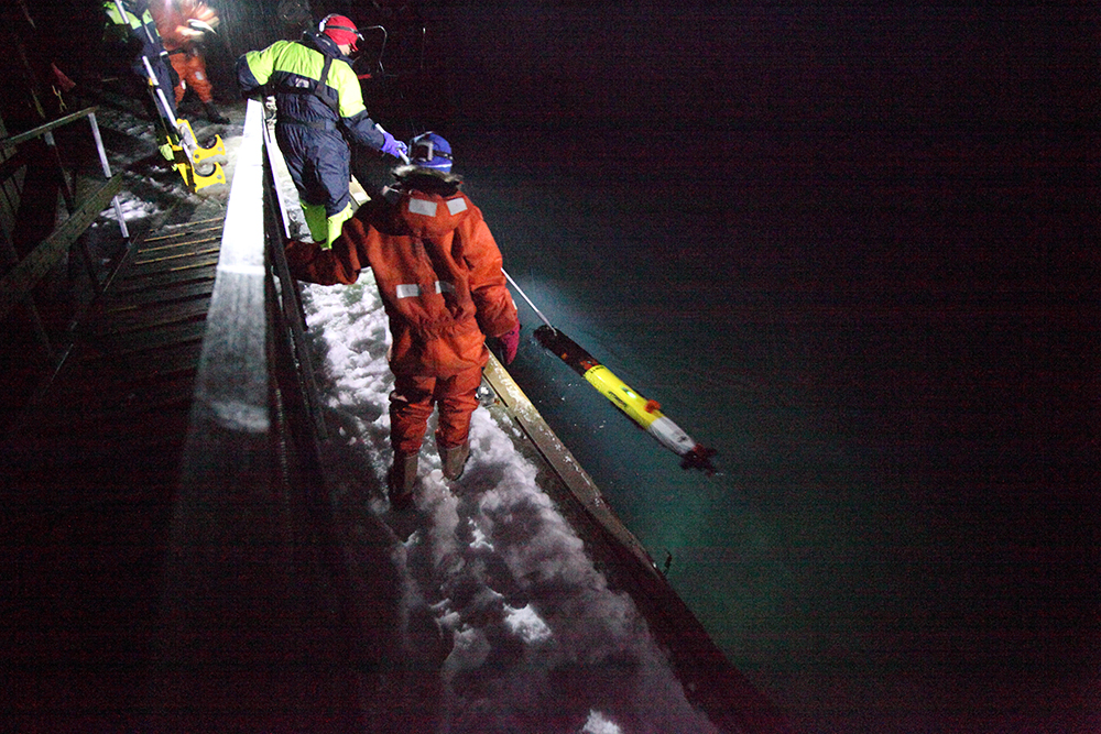 AUV being recovered after mission together with NTNU in Ny-Ålesund during the polar night. Photo: Martin Ludvigsen