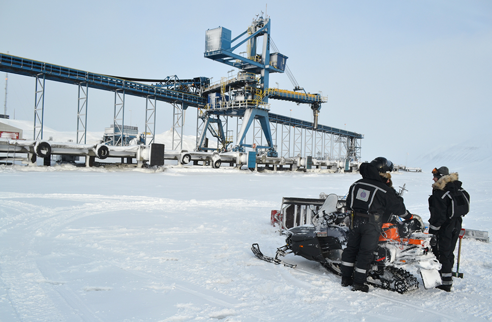 Men, snowmobile and crane in Svea, Svalbard (wintertime)