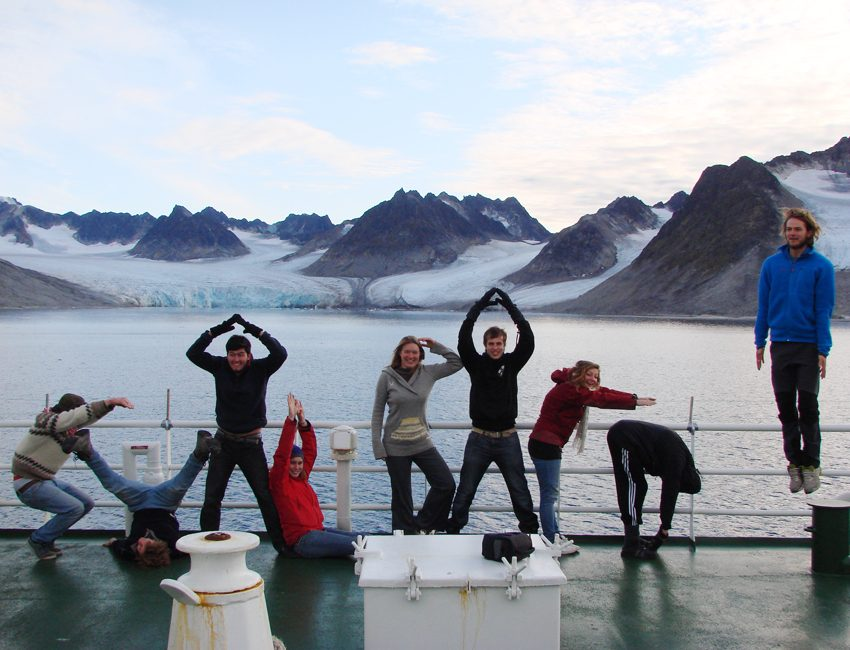 Students on ship deck in front of glacier