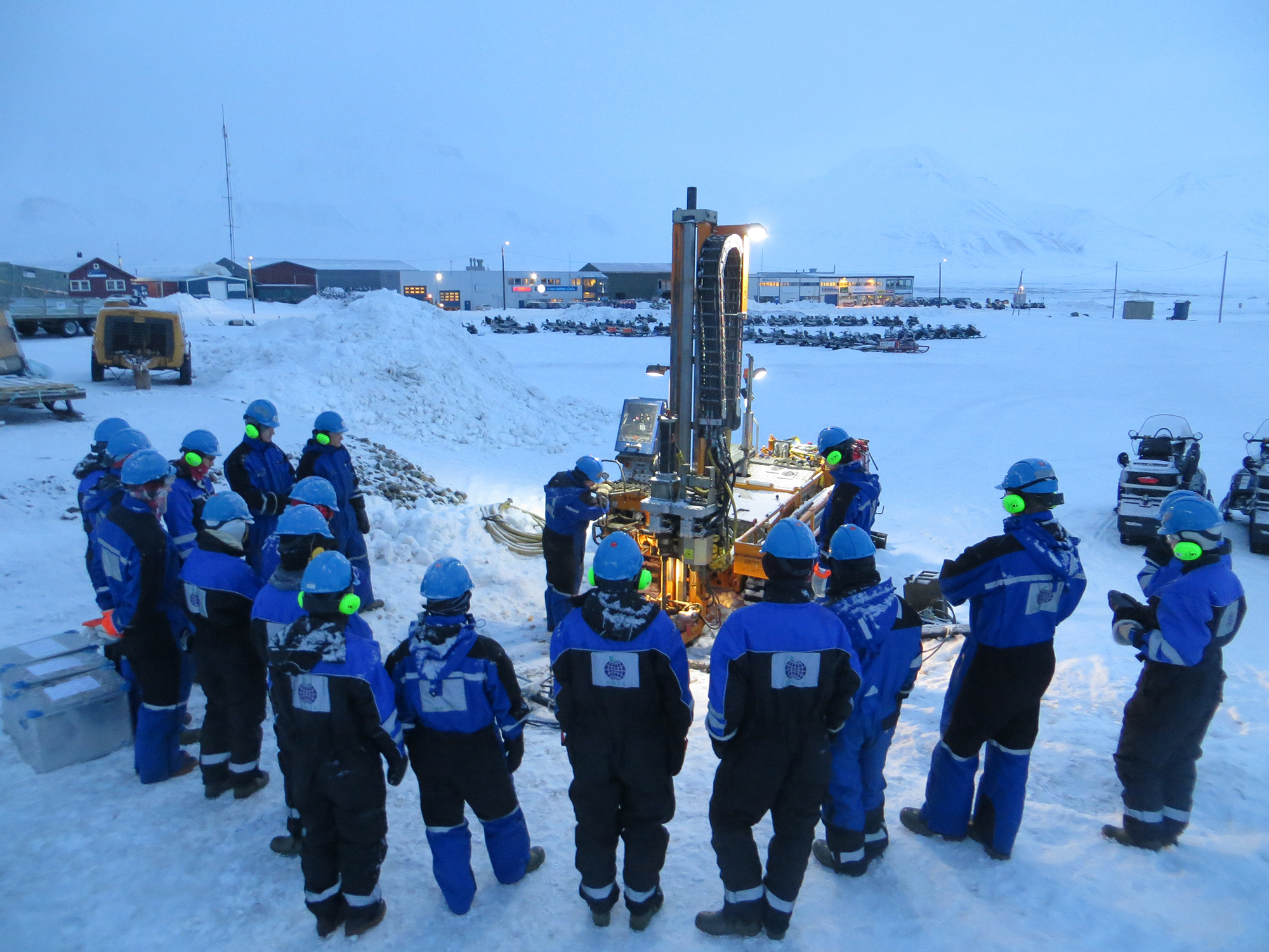Students and researchers at fieldwork in Svalbard, drilling a permafrost core.