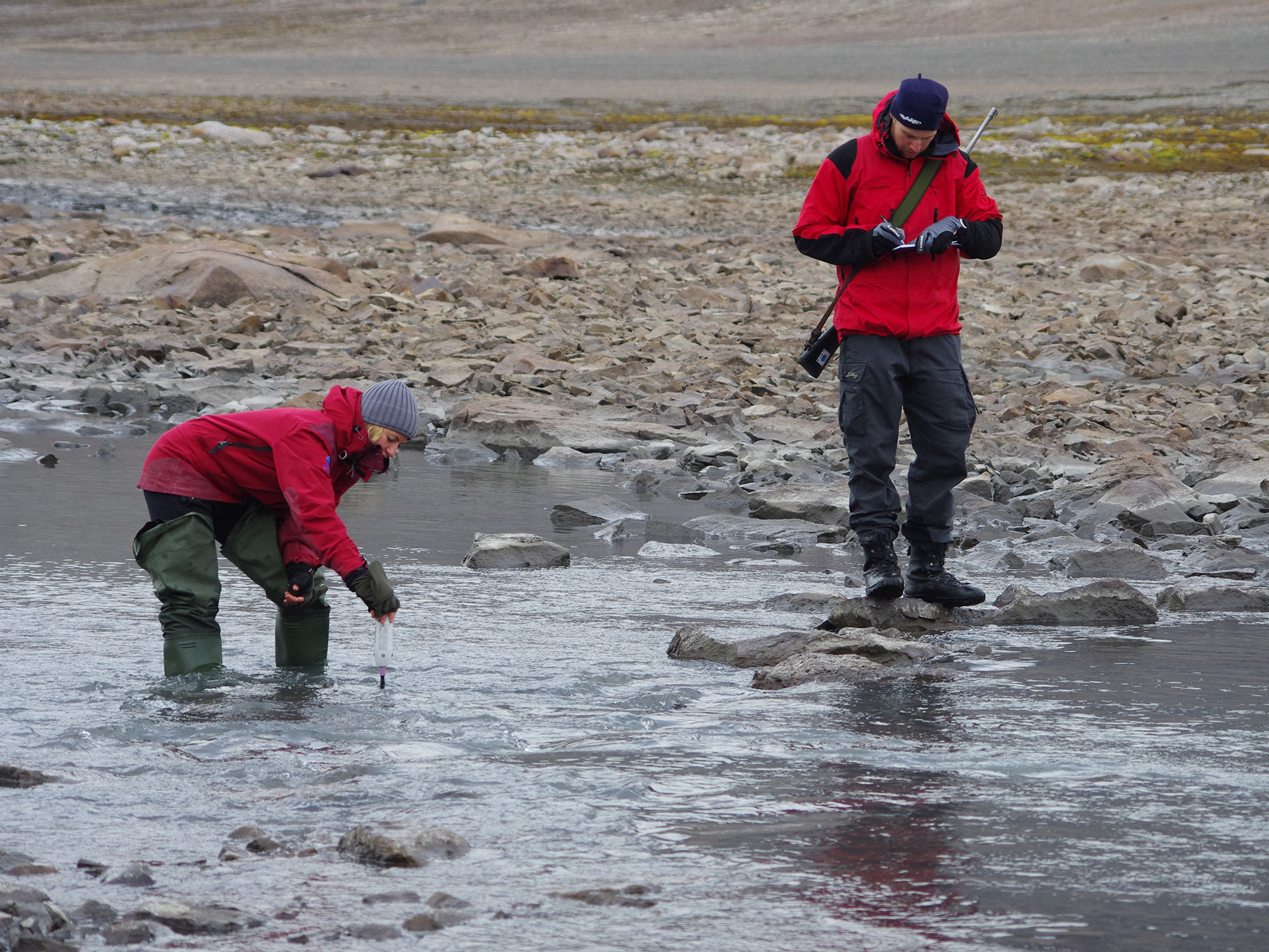 Two people investigating a river in Svalbard.