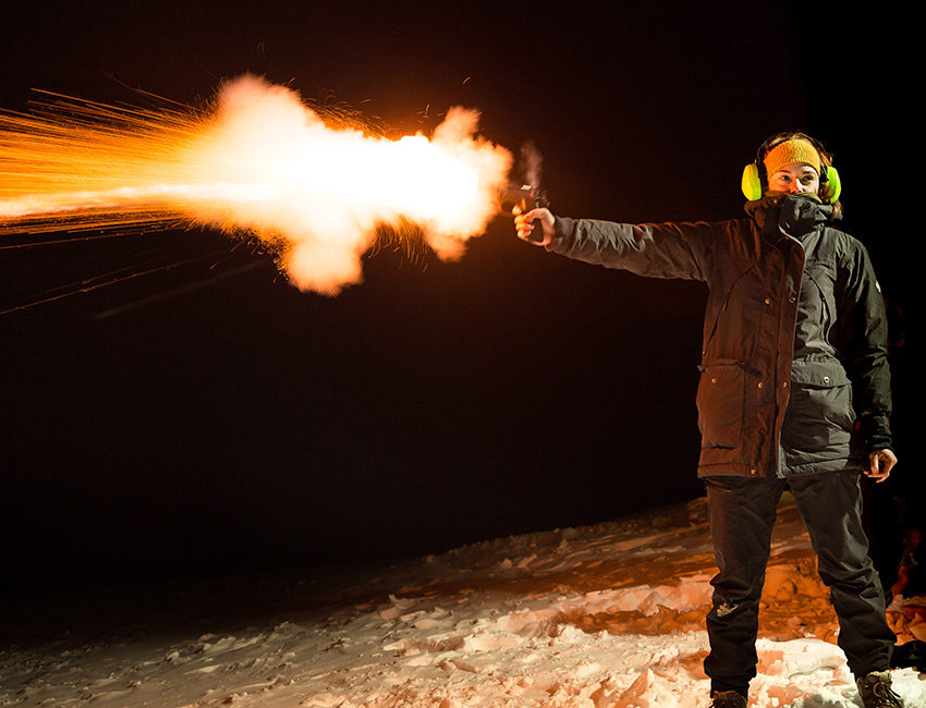 Student firing a signal flare gun during the safety course AS-101 in January 2017. Photo: Børge Damsgård/UNIS
