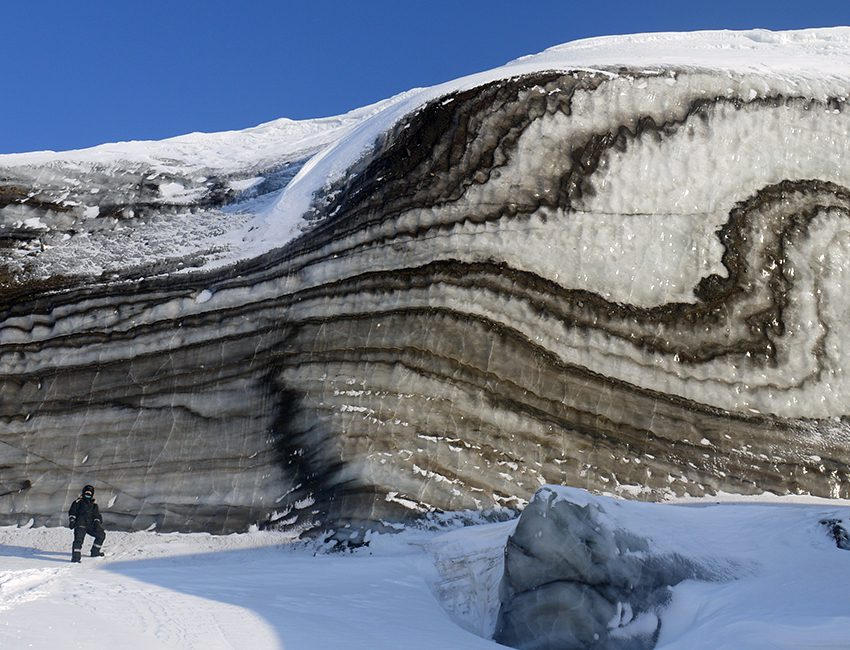 Winter fieldwork insights can be special. Here the clarity of ice structures in a medial moraine deformed by glacier surging has been enhanced by the lack of melting by solar radiation during the dark season. After the onset of summer, the structures become almost invisible. The photo was taken on a snow scooter excursion to Vestre Grønfjordbreen. Photo: Andy Hodson/UNIS