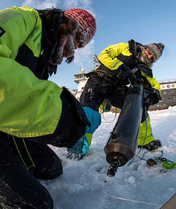 Cheshtaa Chirkara (to the right) working on the sea ice, retrieving a water sampling bottle from an ice hole.